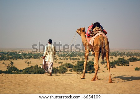 Man with camel in the desert - stock photo