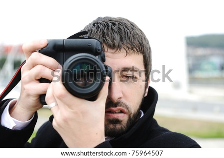 Man with camera outdoor - stock photo