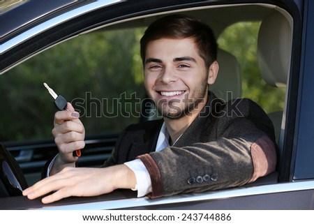 Man with car key in car - stock photo
