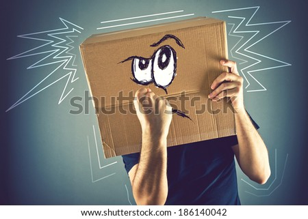 Man with cardboard box on his head and doodle drawing of angry emoticon face. Angry man starting a fight.