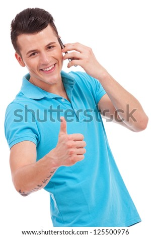 Man with cell phone giving thumb up and smiling to the camera isolated on white - stock photo