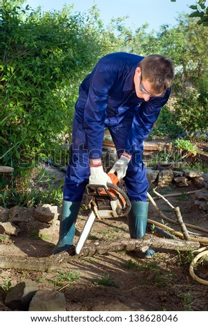 Man with chainsaw cutting the branch - stock photo