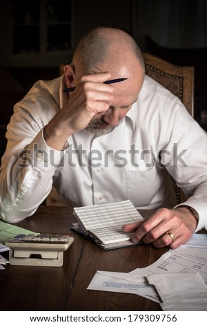 Man with checkbook and calculator concentrating over finances - stock photo
