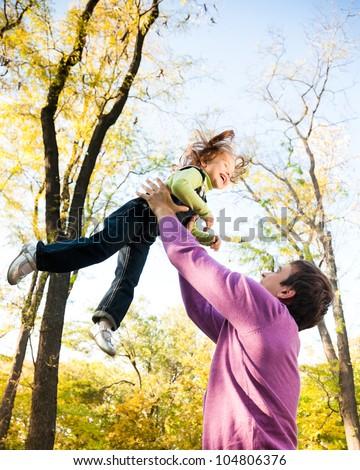 Man with child having fun in autumn park. Focus on man - stock photo