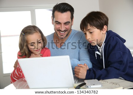 Man with children using laptop at home - stock photo