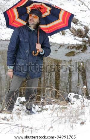 man with colorful umbrella under a snowfall