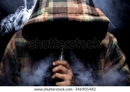 Man with concealed identity smoking a controversial vape.  Vaping is debatable in the health community if it is safe or a health risk.