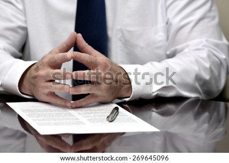 Man with contract or agreement paper with pen wearing white shirt and tie - stock photo