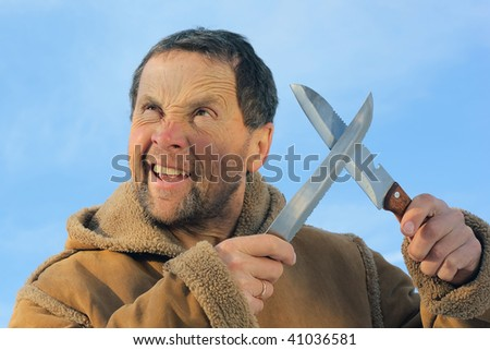 Man with crazy face and two knifes - stock photo