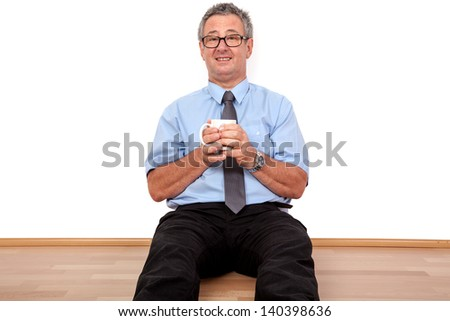 Man with cup sitting on the floor