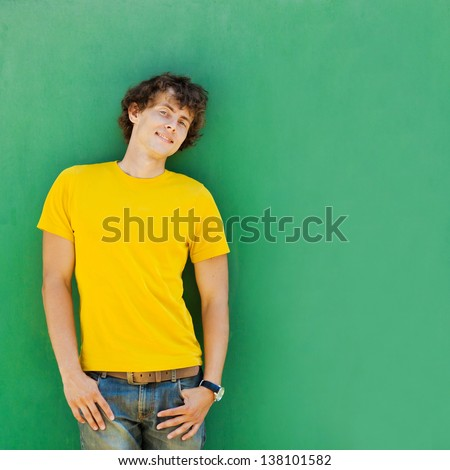 man with curly hair in a yellow T-shirt - stock photo