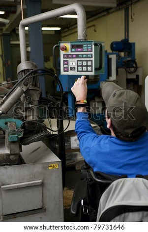 Man with disability operated an industrial machine - stock photo