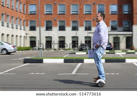 Man with documents with abstract graphics moves on gyroscooter near building at summer, motion blur background
