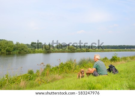 Man with dog sitting in nature river landscape - stock photo