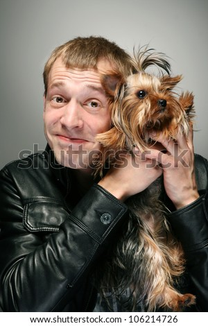 Man with dog. Young man holding dog yorkshire terrier with irony face - stock photo
