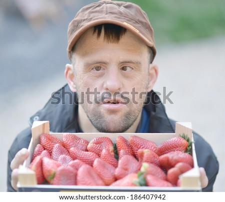man with down syndrome and strawberries - stock photo