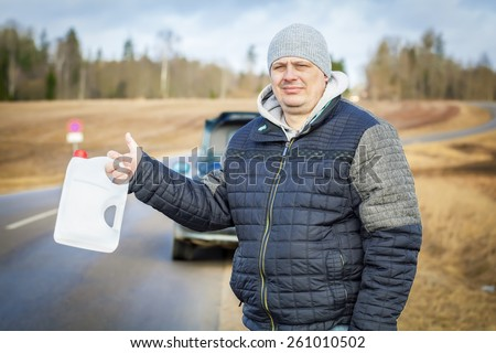 Man with empty can waiting for help near car on the road - stock photo
