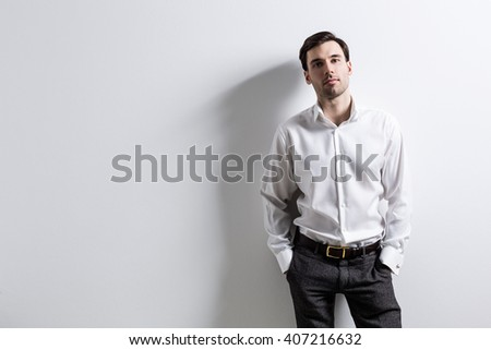 Man with empty wall in the background. Mock up - stock photo
