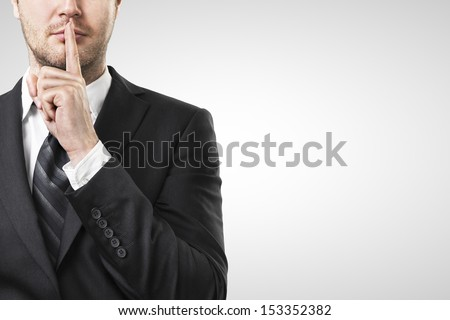 man with finger on lips asking for silence - stock photo