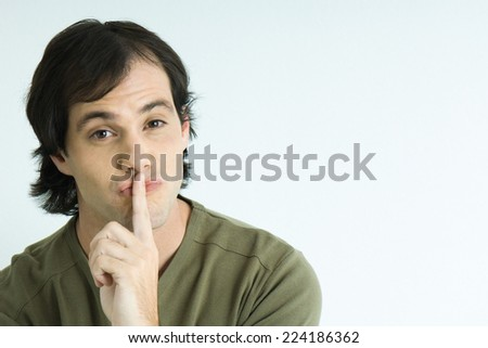 Man with finger over lips, portrait - stock photo