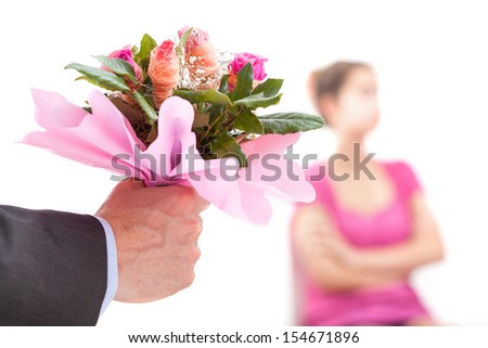 Man with flowers trying to offer an apology to his wife - stock photo