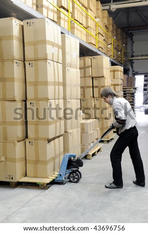 Man with fork pallet truck stacker in warehouse loading Group of cardboard boxes - stock photo