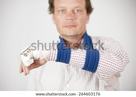 Man with fractured pinky showing pins and bandages with a sad expression. - stock photo