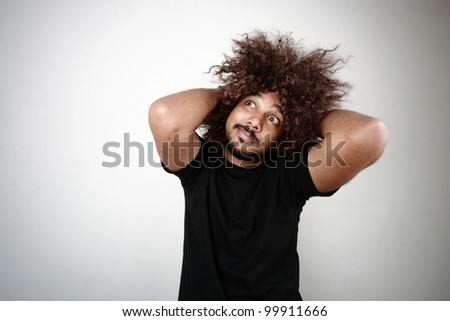 Man with funky hairstyle gives a cool expression