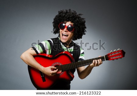 man with funny haircut and guitar - stock photo