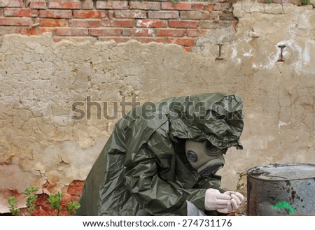 Man with gas mask and green military clothes  explores  small plant  after chemical disaster. - stock photo