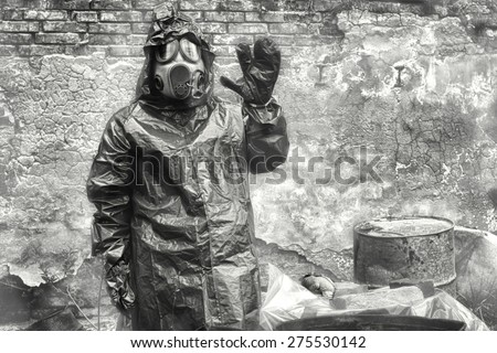 Man with gas mask and  military  clothes  explores  dead bird after chemical disaster.  - stock photo