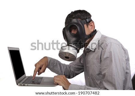 Man with gas mask working with silver laptop isolated on white background - stock photo