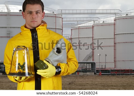Man with gasmask and plant standing at oil reservoirs - stock photo