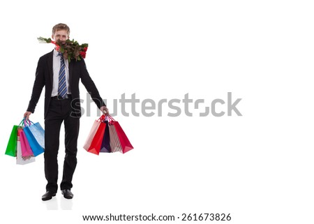 Man with Gift and Flowers on White Background. Handsome Man in a suit and tie in a full-length, Many color Packages in his hands with gifts and a bouquet of flowers on a light background.