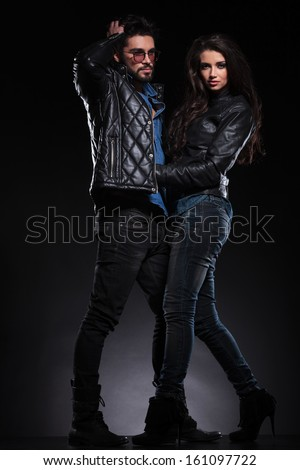 man with glasses and long beard looks away while embracing his girlfriend on dark background - stock photo