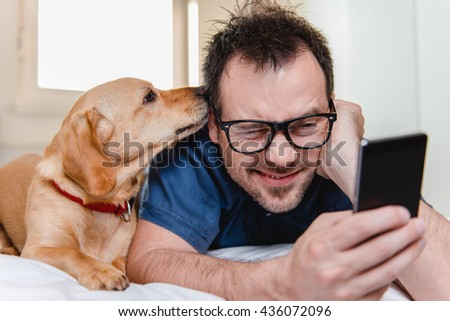 Man with glasses in blue shirt laying on the bed with the dog and using smart phone. - stock photo