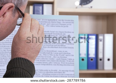 Man with glasses looking at screen - stock photo