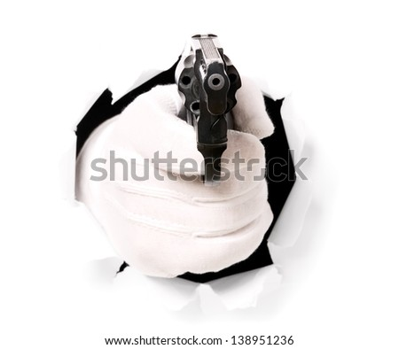 Man with gloves is holding gun through a hole in white paper - stock photo