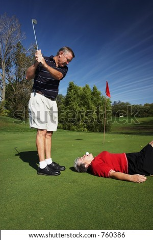 Man with Golf club swinging at woman with ball on her mouth - stock photo