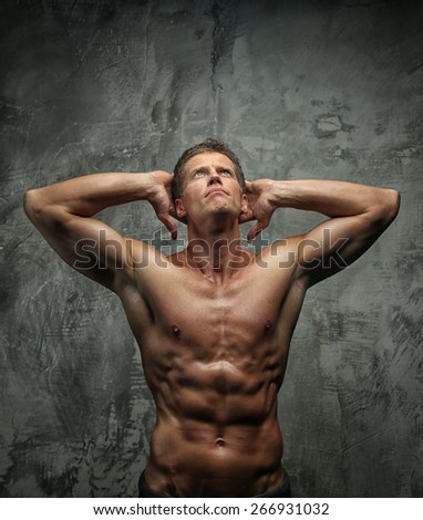 Man with great body antomy posing in studio. Grey background