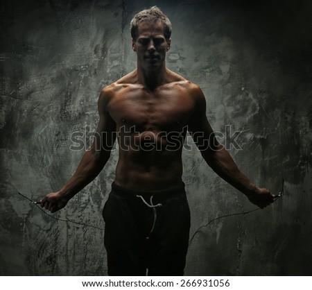Man with great body antomy posing in studio. Grey background - stock photo