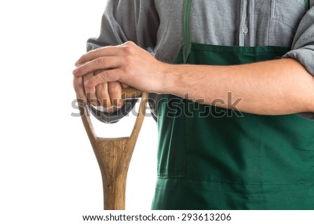 Man with green gardening apron holding spade isolated on white background - stock photo