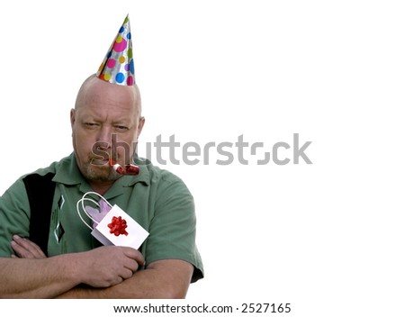 Man with grumpy expression with birthday hat, gift and party favor. - stock photo