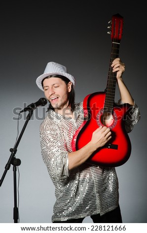 Man with guitar singing with microphone - stock photo