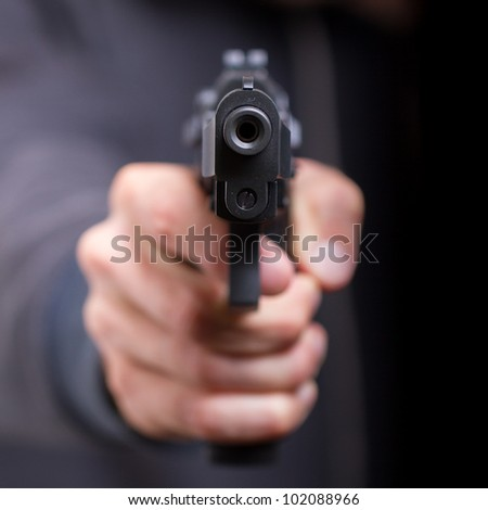Man with gun, gangster, focus on the gun - stock photo