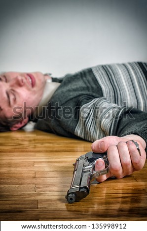 Man with gun laying on the floor - stock photo