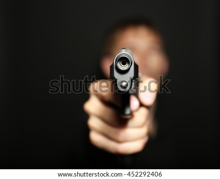 Man with gun on black background - stock photo