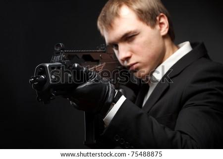 Man with gun over gradient gray. Focused on gun - stock photo