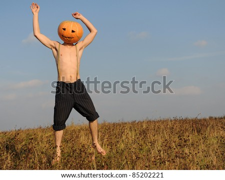 Man with Halloween pumpkin on his head - stock photo