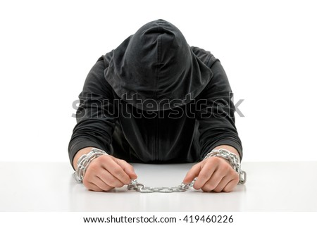 Man with hands in chains is sitting head bowed. Crime and punishment. Offense against the law. Guilt and remorse. Offender in captivity. Restraint of liberty. - stock photo